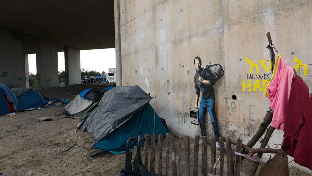 Бэнкси нарисовал Стива Джобса в образе мигранта на стене лагеря для беженцев в Кале